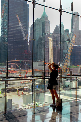 Picture of a woman looking out the large glass paines of the World Financial Center, NYC at construction of the new Freedom Center at Ground Zero.  Photo Credit: Joseph Constantino; Selected as the best of submissions for July, 2011. Published on FreePhotoCourse.com's Contributor's Gallery.  All rights reserved.
