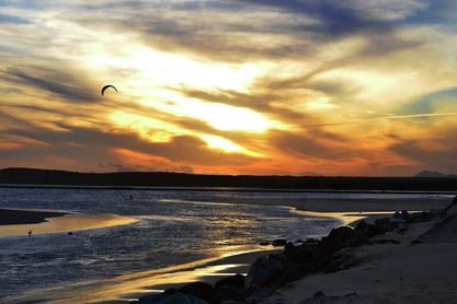 Picture of a kite surfer in front of a sunset at Aston Bay, South Africa.Find more digital photography tips, dslr camera lessons and artistic photo galleries at www.FreePhotoCourse.com.  © 2011, all rights reserved.